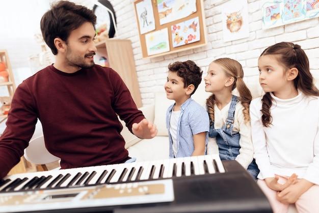Volwassen leraar die piano speelt. Premium Foto