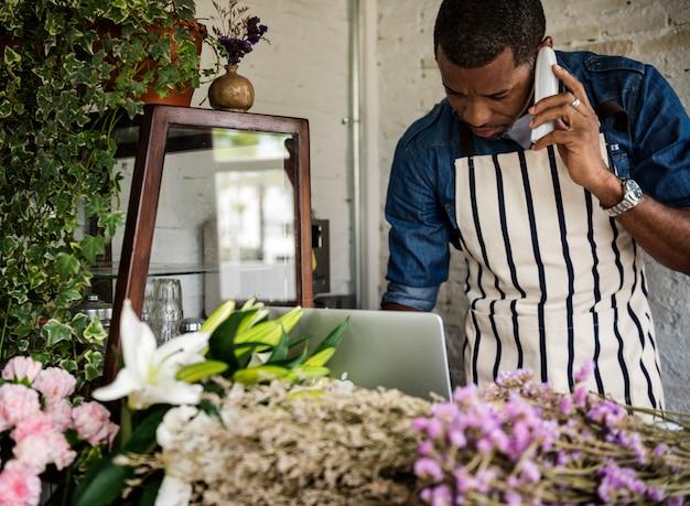 Volwassen man die een bestelling ontvangt, belt in flora shop Premium Foto