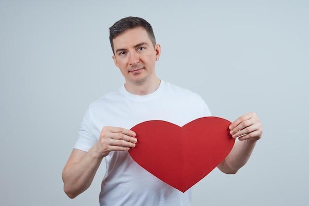 Volwassen man in een wit t-shirt, met een hart van papier in zijn hand, op een grijze achtergrond. fijne valentijnsdag. wereldhartdag. Premium Foto