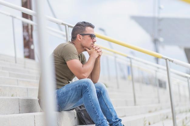 Volwassen man in groen t-shirt zit alleen op trappen buiten en denken Premium Foto