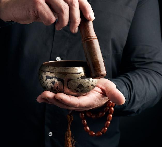 Volwassen man in zwart overhemd draait een houten stok om een koperen tibetaanse kom met water. ritueel van meditatie Premium Foto