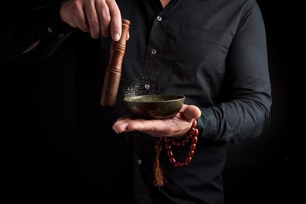 Volwassen man in zwart overhemd draait een houten stok om een koperen tibetaanse kom Premium Foto