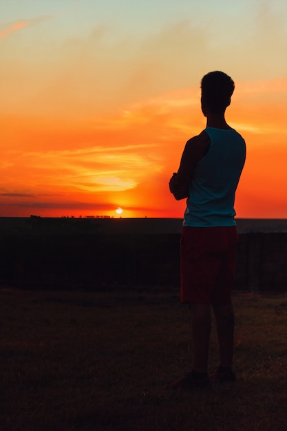 Volwassen man kijken naar de zonsondergang Premium Foto