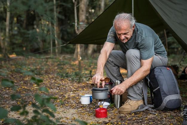 Volwassen man koken op een camping Premium Foto