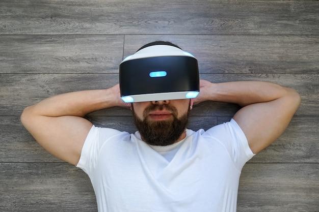 Volwassen man liggend op zijn rug in virtuele glazen door sony playstation vr headset Premium Foto