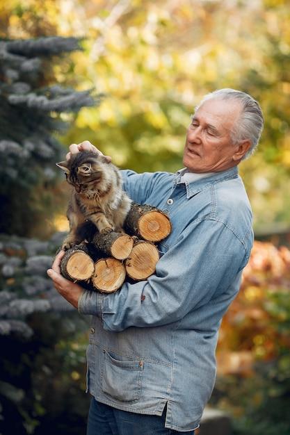 Volwassen man met brandhout en een kat Gratis Foto