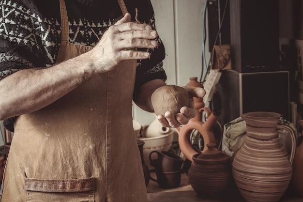Volwassen mannelijke pottenbakkersmeester die de klei fijnstampen Premium Foto