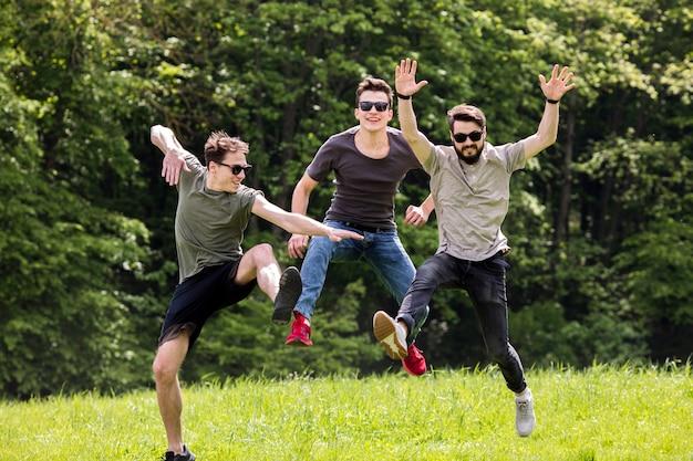 Volwassen mannen die in aard springen en in medio lucht stellen Gratis Foto