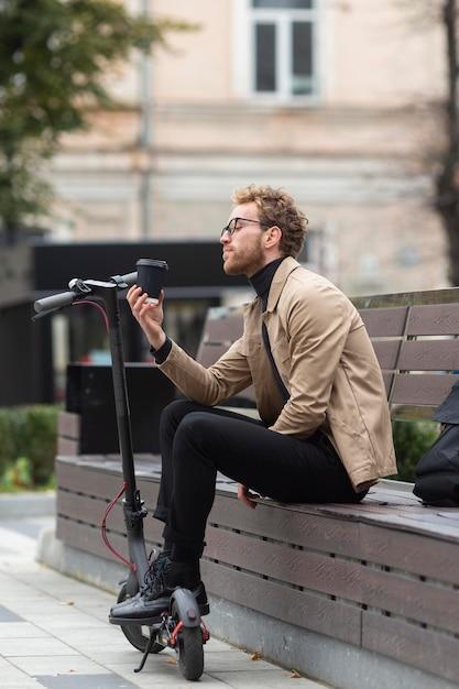 Volwassen mannetje dat van een koffie in openlucht geniet Gratis Foto
