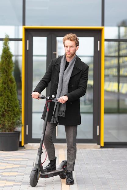 Volwassen mannetje poseren met een elektrische scooter Gratis Foto
