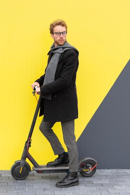 Volwassen mannetje poseren met zijn elektrische scooter Gratis Foto