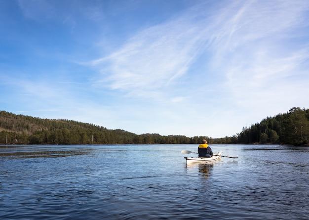 Volwassen mens die noorse rivier in witte kajak in nidelva peddelen, noorwegen Premium Foto