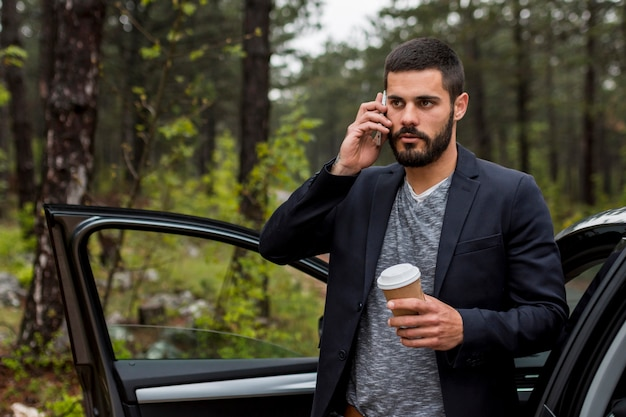 Volwassen mens die op telefoon dichtbij geopende autodeur spreekt Gratis Foto