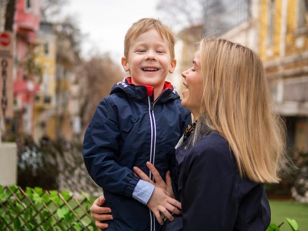 Volwassen moeder die haar jonge jongen in openlucht houdt Gratis Foto
