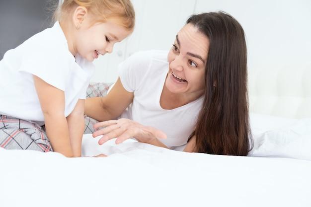 Volwassen moeder spelen met actieve dochtertje in bed thuis, met plezier, activiteit met kinderen. Premium Foto