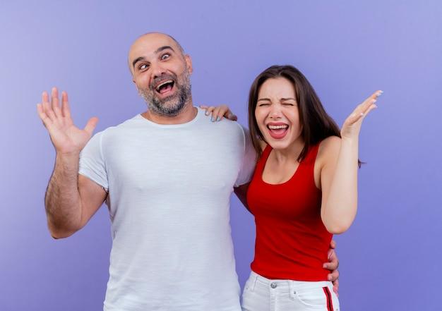 Volwassen paar speelse man met lege hand met gekruiste ogen en geïrriteerde vrouw hand op zijn schouder zetten en lege hand met gesloten ogen tonen Gratis Foto