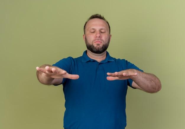 Volwassen slavische man die zijn handen uitstrekt naar, lopend met gesloten ogen Gratis Foto