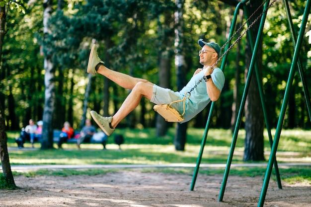 Volwassen stijlvolle man in glazen rijden op schommel in stadspark op speelplaats voor kinderen in de zomer. Premium Foto