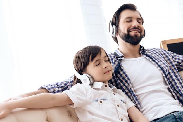 Volwassen vader en tiener die aan muziek op hoofdtelefoons luisteren. Premium Foto