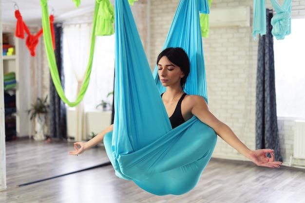 Volwassen vrouw beoefent anti-zwaartekracht yoga Gratis Foto