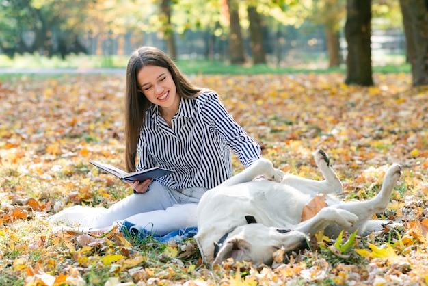 Volwassen vrouw die haar hond in het park aait Gratis Foto