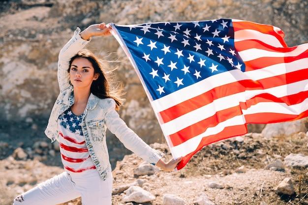Volwassen vrouw die handen met de vlag van de vs opheffen Gratis Foto