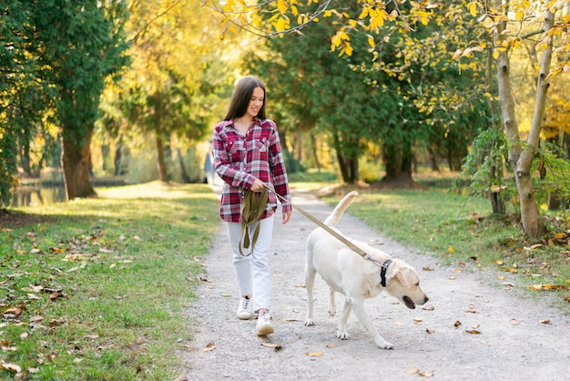Volwassen vrouw die in het park met haar hond loopt Gratis Foto