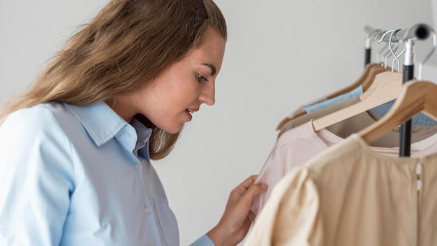 Volwassen vrouw die nieuwe kleren controleert Gratis Foto