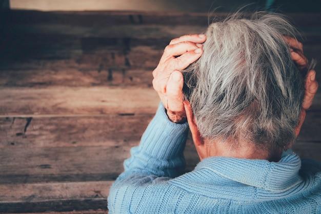 Volwassen vrouw heeft hoofdpijn. ze zat met haar handen op een donkere zwarte kamer. concept dramatische eenzaamheid, verdriet, depressie, trieste emoties, huilen, teleurgesteld, gezondheidszorg, pijn. Premium Foto