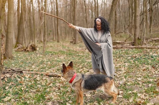 Volwassen vrouw in een de lentebos met hond Gratis Foto