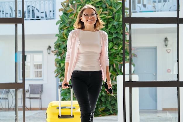 Volwassen vrouw met bagage met koffer die naar de hotellobby gaat, vrouw die met zakenreis reist Premium Foto