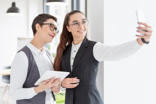 Volwassen vrouwen die een selfie nemen op kantoor Gratis Foto