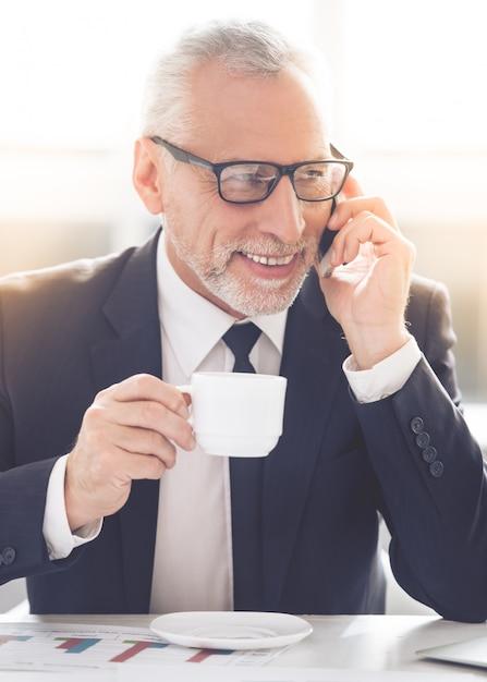 Volwassen zakenman houdt een beker Premium Foto