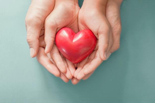 Volwassene en kind handen met rood hart, gezondheid van het hart, donatie, gelukkige vrijwilligers liefdadigheid, csr sociale verantwoordelijkheid, wereld hart dag, wereld gezondheid dag, wereld geestelijke gezondheid dag, pleeggezin Premium Foto