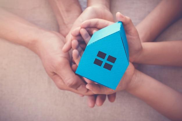 Volwassene en kind handen met witte huis, familie thuis en dakloze onderdak concept Premium Foto