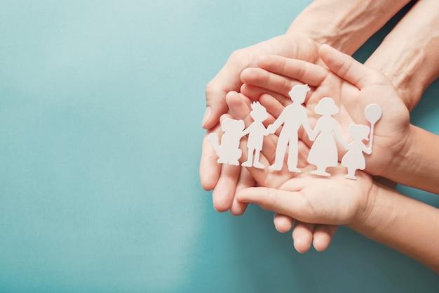 Volwassene en kinderenhanden die document familieknipsel, familiehuis, goedkeuring, pleegzorg houden. Premium Foto