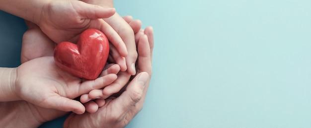 Volwassene en kindhanden die rood hart op aquaachtergrond houden Premium Foto