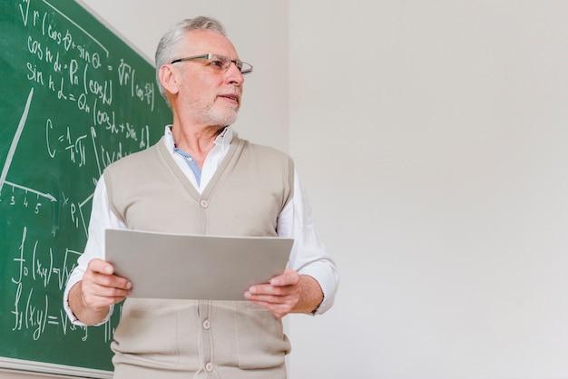 Vooraanstaande wiskundeleraar fronsen met vellen papier Gratis Foto