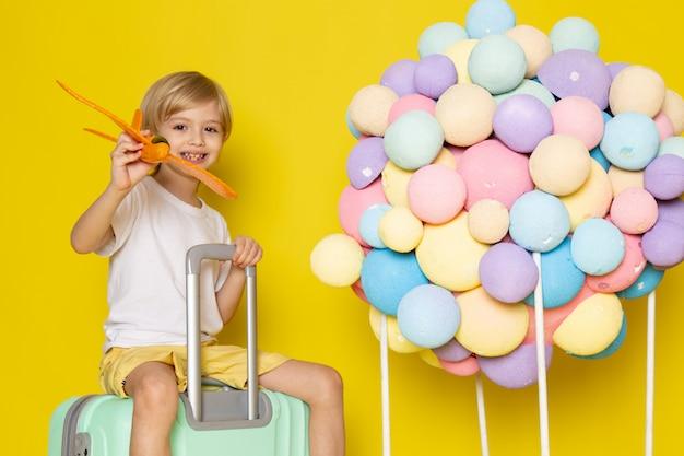 Vooraanzicht blonde glimlachend kind in wit t-shirt spelen met vliegtuig op het gele bureau Gratis Foto