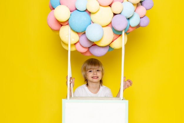 Vooraanzicht blonde jongen in wit t-shirt samen met kleurrijke lucht ballonnen op de gele Gratis Foto