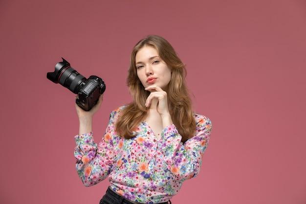 Vooraanzicht blonde vrouw kijkt rechtstreeks met haar camera Gratis Foto