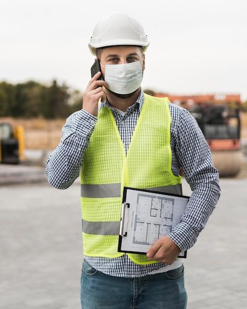 Vooraanzicht bouwer man praten over de telefoon Gratis Foto