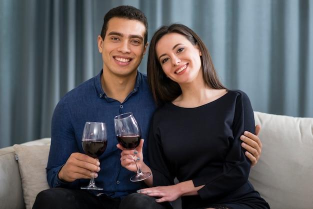 Vooraanzicht ccouple met een glas wijn zittend op de bank Gratis Foto