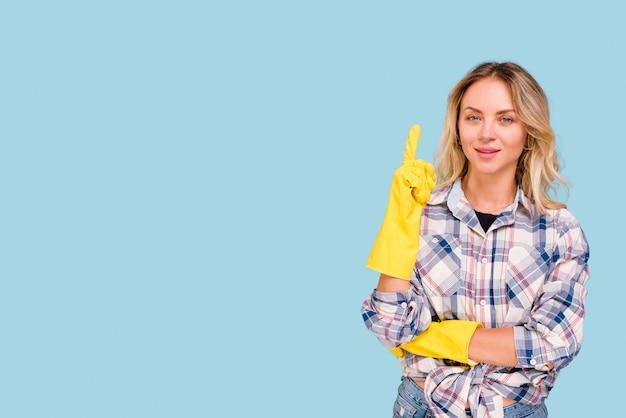 Vooraanzicht dat van jonge vrouw naar omhoog het bekijken camera over blauwe achtergrond richt Gratis Foto