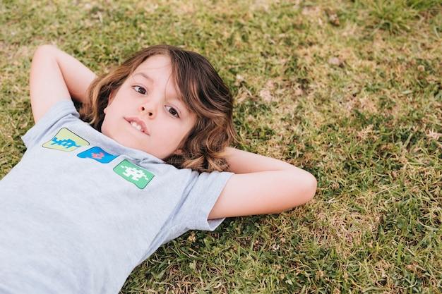 Vooraanzicht dat van jongen op gras ligt Gratis Foto
