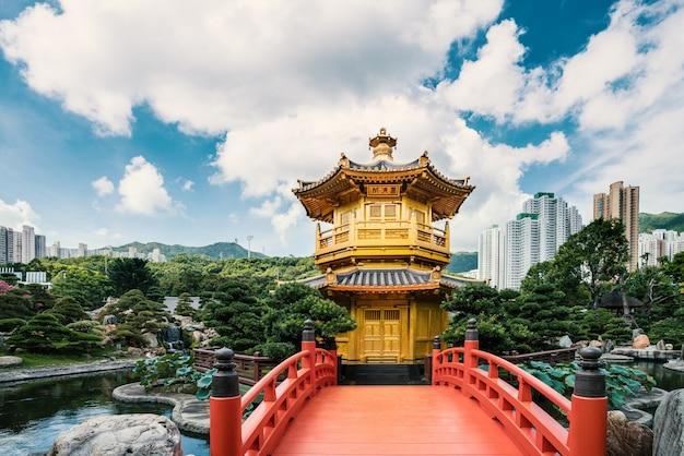 Vooraanzicht de gouden paviljoenstempel met rode brug in nan lian-tuin, hong kong. aziatisch toerisme, het moderne stadsleven, of bedrijfsfinanciën en economieconcept Premium Foto