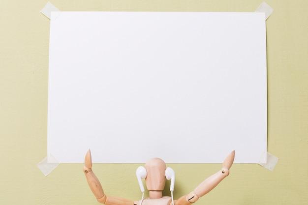 Vooraanzicht die van marionet een aanplakbiljet houdt Gratis Foto