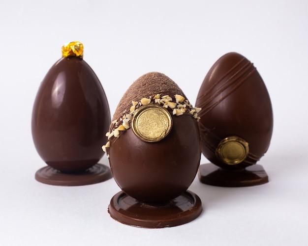 Vooraanzicht drie versierde chocolade-eieren met noten en goud op stand Gratis Foto