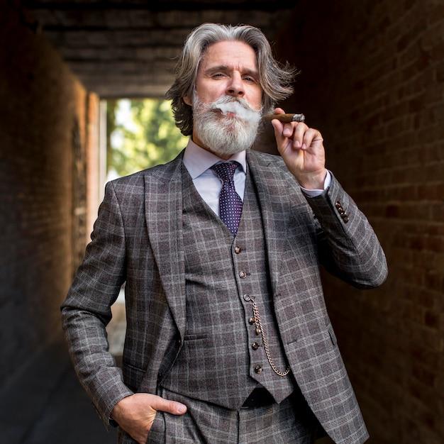 Vooraanzicht elegante volwassen man roken Gratis Foto