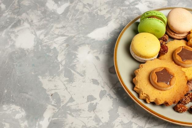 Vooraanzicht franse macarons met cakes en koekjes op witte ondergrond Gratis Foto